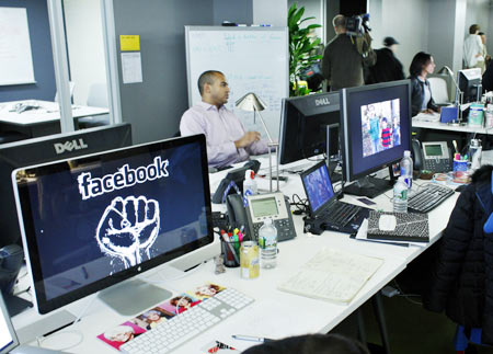 Facebook workers sit at their desks before a news conference at their office in New York December 2, 2011.