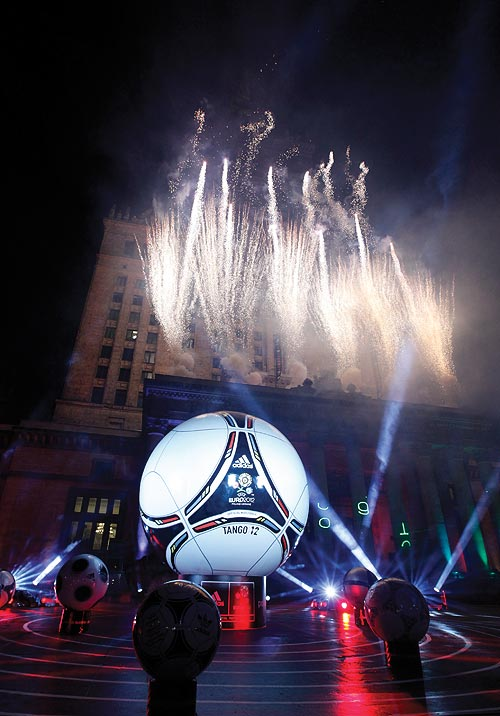 A giant Tango 12 soccer ball, which was unveiled on Friday as the official ball for Euro 2012, is displayed in front of the Palace of Culture in Warsaw December 2, 2011. The Tango 12 is based on a classic design used at the World Cup and European championships of the 1980s. It features a modern interpretation of the hugely popular Tango design of the past with the colours of the flags of the two co-hosts incorporated into its design: red and white for Poland and yellow and blue for Ukraine. Picture taken December 2, 2011.