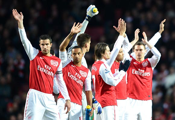 Robin van Persie and Theo Walcott of Arsenal wave ahead of the Barclays Premier League match between Arsenal and Wigan Athletic at Emirates Stadium on April 16, 2012 in London, England.