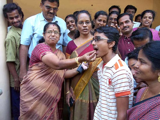 Venkatanathan Srinath (in striped tshirt) being offered sweets at school