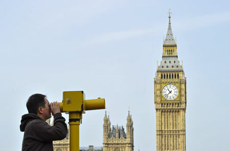 A man looks through a telescope opposite Big Ben and the Houses of Parliament, in central London