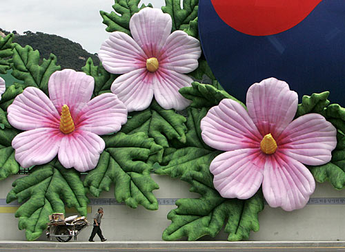 A man pulls a cart as he walks along sculptures of Roses of Sharon covering the fences of Gyeongbokgung palace in Seoul.