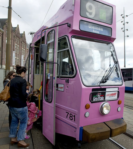 A woman and her children board a tram painted pink in Amsterdam to celebrate the arrival of the Giro d'Italia in Amsterdam