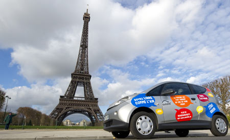 A Paris Autolib' electric car is parked near the Eiffel tower during a presentation ride in Paris