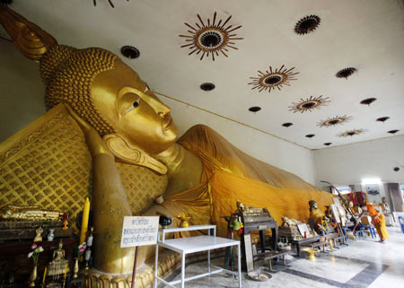 A Buddhist monk sweeps the floor next to a giant statue of Buddha at Klang Kret temple in Nonthaburi province, on the outskirts of  Bangkok