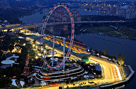 An aerial view shows the main grand stand and the F1 pit building behind the Singapore Flyer observation wheel at dusk