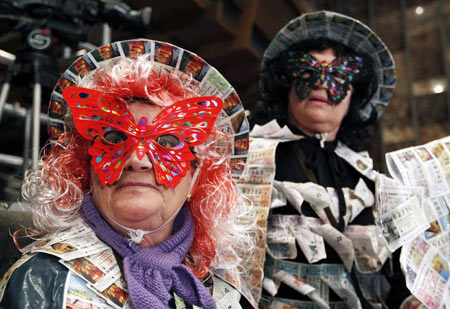 Women in costumes adorned with old lottery tickets attend the draw for Spain's Christmas Lottery