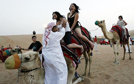 A keeper helps tourists dismount from a camel in the Dubai desert