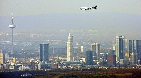 A Lufthansa Boeing 747 passenger plane lands in front of Frankfurt's skyline