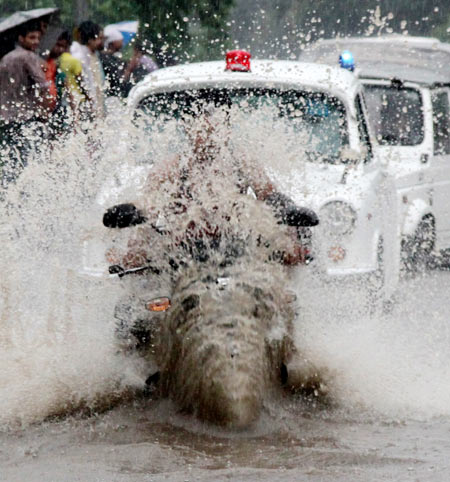 A man rides his bike through a flooded road during heavy rains in New Delhi