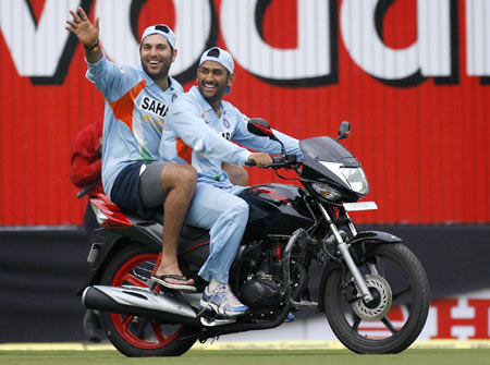 Yuvraj Singh (L) and India's captain Mahendra Singh Dhoni ride a bike which was given to Yuvraj Singh for winning the man-of-the-match award following India's win in the second one-day international cricket match against England in Indore