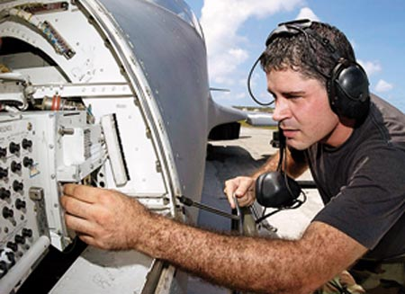 An engineer inspects the circuit of an airplane