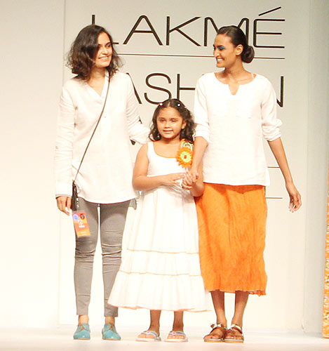 Priyadarshini Rao (left) poses with a kid and model Rachael Bayros (right)