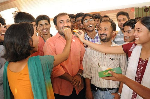 Anand Kumar is offered sweets by his students
