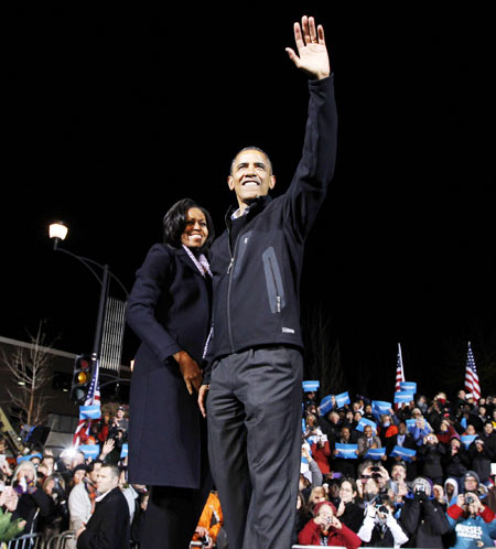 US President Barack Obama waves to supporters as he stands next to first lady Michelle Obama during his final presidential campaign rally in Des Moines, Iowa, November 5, 2012, on the eve of the US presidential elections.