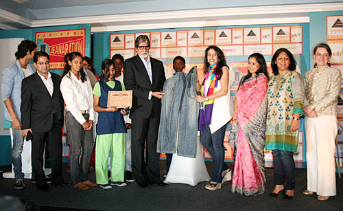 Amitabh Bachchan and Shobhaa De display the jeans they are auctioning for Parikrama at the event, flanked by students and administrators of the school