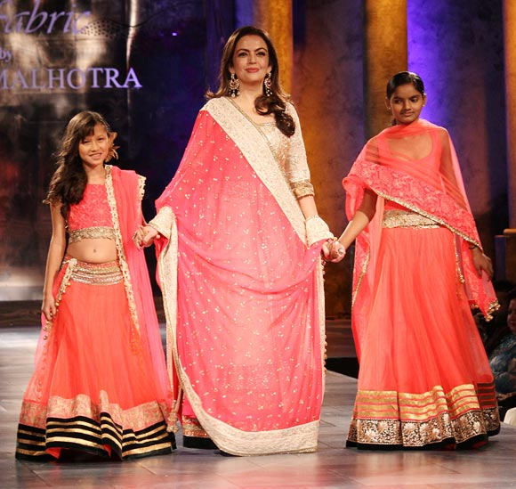 Nita Ambani walks the ramp for Manish Malhotra, escorting two young girls from the village of Mijwan down the runway at the Mijwan -- Sonnets in Fabric showing in Mumbai last night