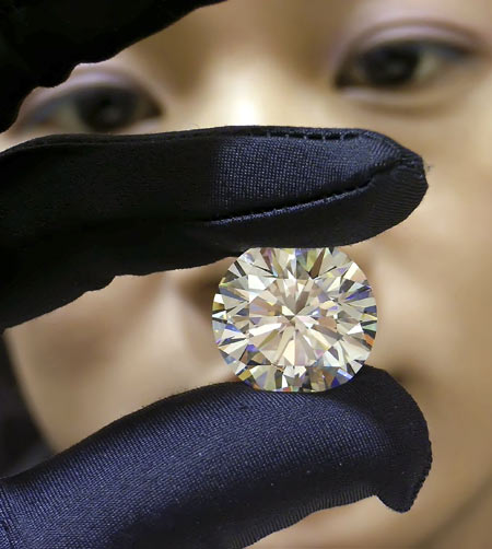 A saleswoman displays a 26.62 carat diamond at a shopping centre in Nanning, south China's Guangxi province. The diamond is valued at 41,200,000 yuan ($5,253,000) and belongs to a Belgian company.