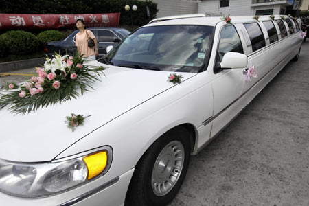A woman looks on near a Lincoln limousine ferrying a couple for their wedding