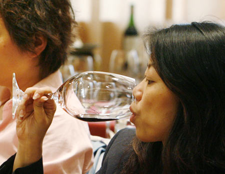 Wine lovers try red wine during a Chateau Haut Brion wine-tasting event in Beijing