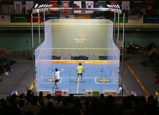 South Korea's Kim Hyun-dong plays against Macau's Lao Chi Hang (L) during the men's team squash third and fourth placing match at the East Asian Games in Hong Kong December 9, 2009.