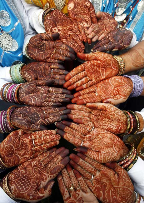 Indian women folk dancers show their hands decorated with henna paste before their performance at a cultural program organised during the festival of Teej.