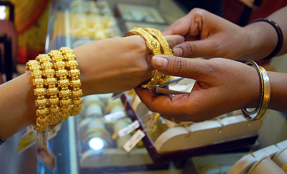 A married Hindu woman wears gold bangles at a jewellery shop on the eve of the festival of Teej