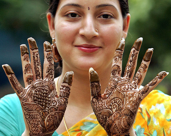 A Hindu woman shows her hands decorated with henna paste ahead of Teej festival on month of Shravan