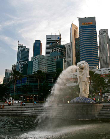 People sit on the steps near the Merlion, in Singapore's financial district
