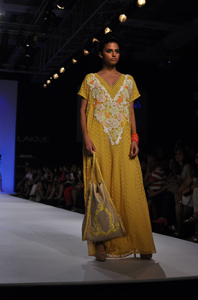 A model presents a pale yellow maxi by Ranna Gill from her Mauritius collection