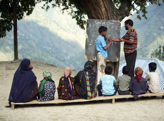 A teacher teaches counting techniques to a deaf and mute boy at an open air class at Dadhkai Village in the Doda district, 260 km (162 miles) north of Jammu, June 18, 2009. Silence reigns in this sleepy village nestled high up in the Himalayan mountains in northern India and where the majority of residents are either deaf or mute. Each of the 47 families in this village in Jammu and Kashmir state have a least one member who can neither hear nor speak. The first reported case dates back to 1931 and now the numbers have swelled to 82.