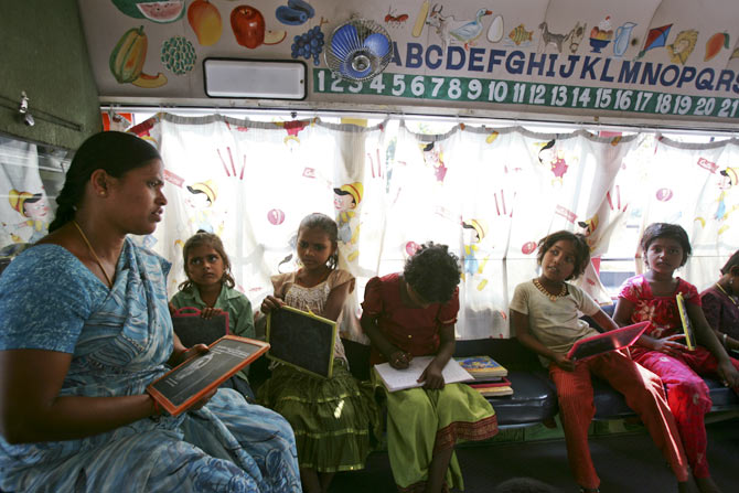 Teacher H. Laxmi conducts lessons inside a bus which has been converted into a school called School on Wheels at a slum area in the southern Indian city of Hyderabad November 1, 2011. The mobile school, run by CLAP Foundation, a non-governmental organisation, brings education to the doorstep of disadvantaged children every day, halting for several hours at a time in different parts of the sprawling city. The children, whose parents are day labourers on construction sites, or work as rag pickers and maids, either never go to school or drop out once enrolled. Many have to work as hard as their parents to pay off family debts.