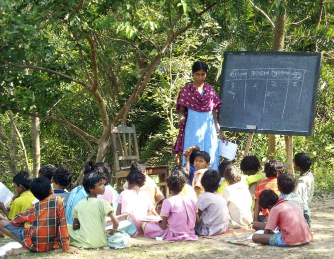 Children sit on the ground in a outdoor school during a lesson in Santiniketan village in this undated handout photograph. In Santiniketan village in West Bengal -- the home of Nobel literature prize winner Rabindranath Tagore -- a voluntary initiative helping local Kora and Santhali tribal children to read and write Bengali is now so popular it needs a second building.