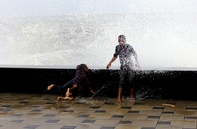Children have a ball as huge waves hit the promenade at Mumbai's Worli Sea Face.