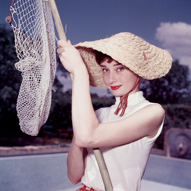 Portrait of Belgian-born American actress Audrey Hepburn (1929 - 1993) as she wears a peculiar hat and sleeveless blouse and holds a pool cleaning net beside a dry swimming pool, early 1950s.