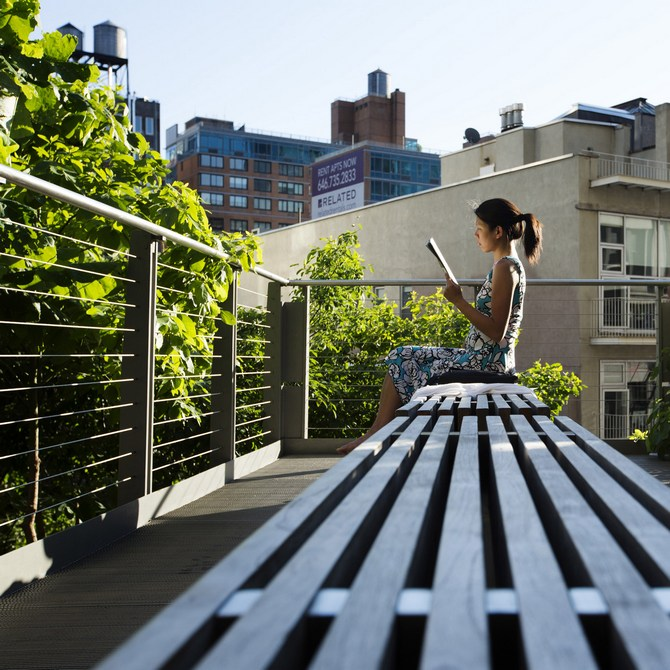 A woman uses the late afternoon sun to read while sitting on the High Line park in New York.