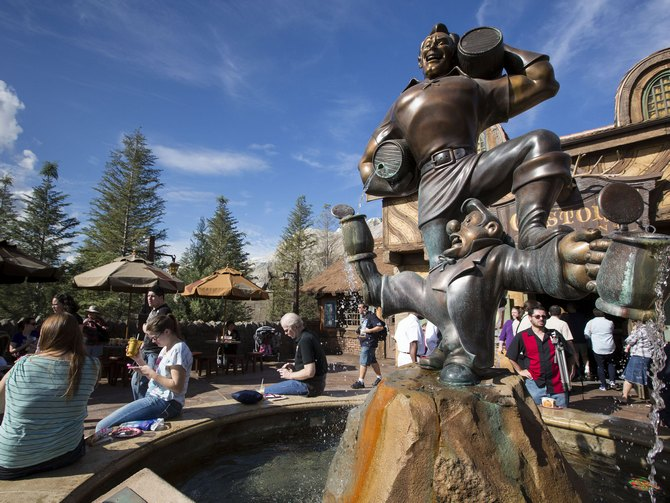 Guests gather around a fountain near Gaston's Tavern following the grand opening ceremony for Walt Disney World's new Fantasyland in Lake Buena Vista, Florida