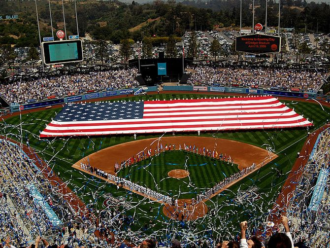 Sailors and Marines unfurl a football field-sized American flag at Dodger Stadium during the pre-game activities before a Major League Baseball game between the Los Angeles Dodgers and the San Francisco Giants.