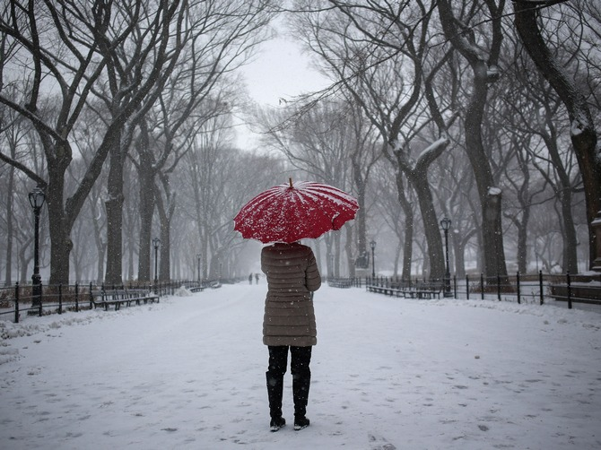A woman stands with an umbrella during snowfall at Central Park in New York.
