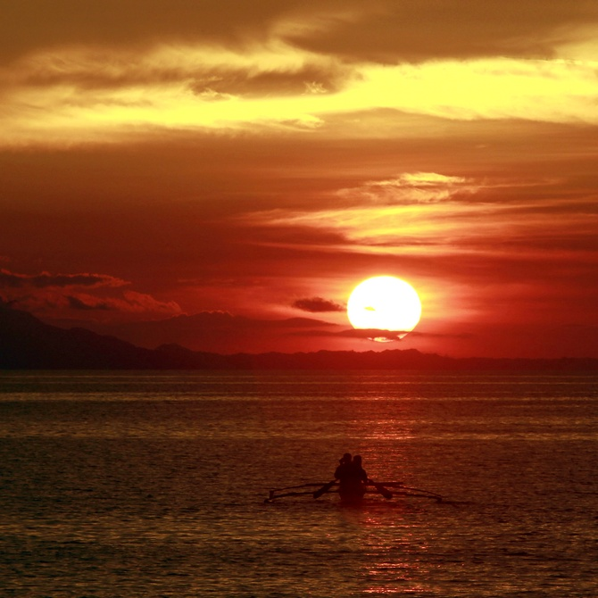 Residents paddle their canoe to go fishing as the sun sets in Mogpog town on Marinduque island, south of Manila, the second largest city of the Philippines.