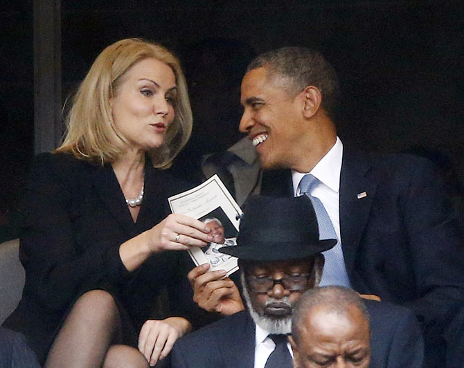 U.S. President Barack Obama (C) shares a laugh with Danish Prime Minister Helle Thorning-Schmidt (L) as his wife, U.S. first lady Michelle Obama looks on during a memorial service for late South African President Nelson Mandela at the FNB soccer stadium in Johannesburg December 10, 2013. Picture taken December 10.