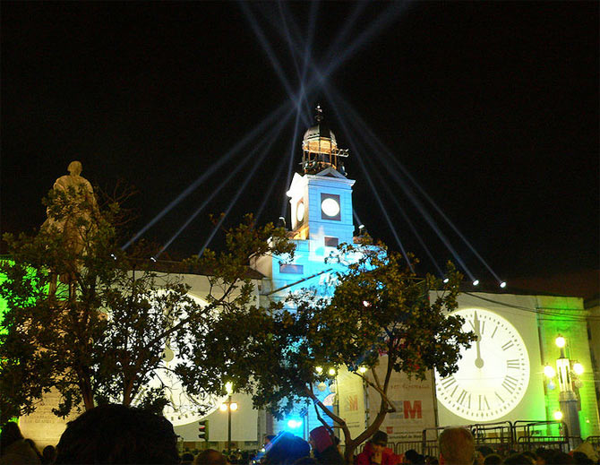 The clock on top of the Casa de Correos building is lit up for New Year