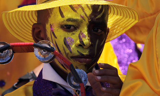 A child waits as brightly coloured revellers sing and dance through the streets of Cape Town during the New Year