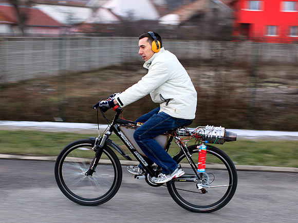 Raul Oaida starts his bicycle propelled with a self-built jet engine in the yard of his house in Deva