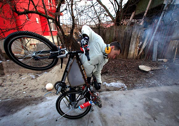 Raul Oaida prepares his bicycle propelled with a self-built jet engine to be tested on a road in the back of his house in Deva, 399 km (245 miles) of Bucharest.