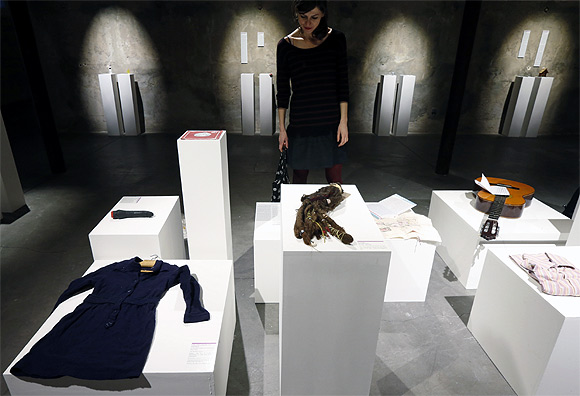 A visitor looks at articles which are displayed at the Museum of Broken Relationships installed at the CentQuatre exhibition hall in Paris.