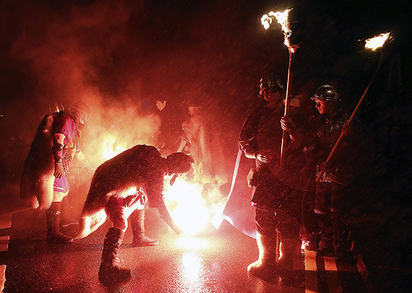 Jarl Squad vikings light up their torches during the Up Helly Aa fire festival in Lerwick, Shetland Islands, Scotland.