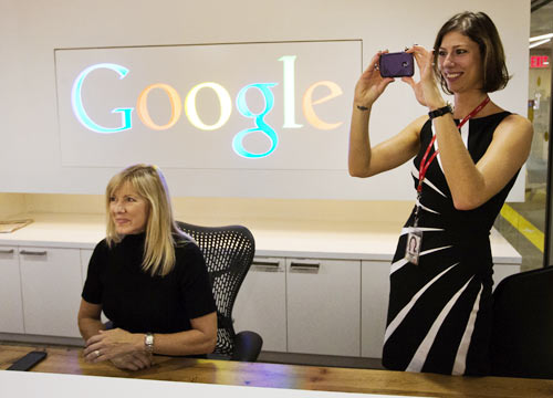 Google employee Andrea Janus takes a picture with her phone as her co-worker Tracy McNeilly looks on at the new Google office in Toronto, November 13, 2012.