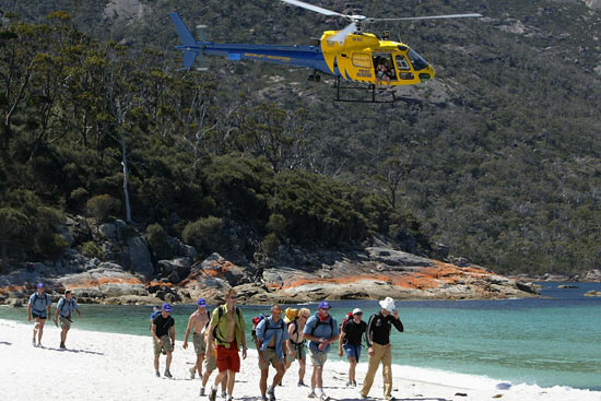 Participants on the beach at Wineglass Bay with the TV helicopter close by, during The Cadbury Schweppes Mark Webber Challenge on November 15, 2003 in Tasmania, Australia.