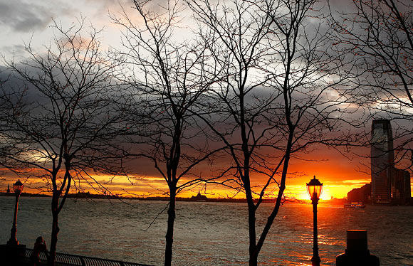 A woman stops to watch the sun set over New Jersey from Battery Park in New York